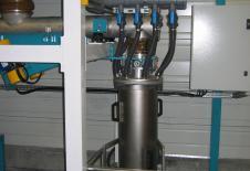 Dosificació de material en pols per dosificador vibrant a la sortida del dispositiu de buidatge